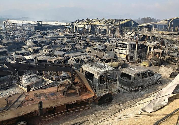 Scrapped vehicles burnt by a forest fire are seen at an auto junkyard in Sokcho (AFP Photo/YONHAP)