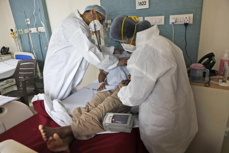 Dr. Kedar Toraskar checks a COVID-19 patient at the Mumbai Central Wockhardt Hospital in Mumbai, India, June 4, 2021. The recent coronavirus surge in India affected young people on a scale his team of critical care doctors hadn't previously seen. (AP Photo/Rajanish Kakade)