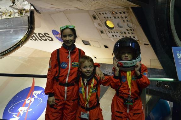 Sofia and Matthew Bogle, ages 9 and 6, and John John Humphries, 5, dressed up for the opening of the Space Shuttle Atlantis exhibition at Kennedy Space Center in Florida on June 29, 2013.