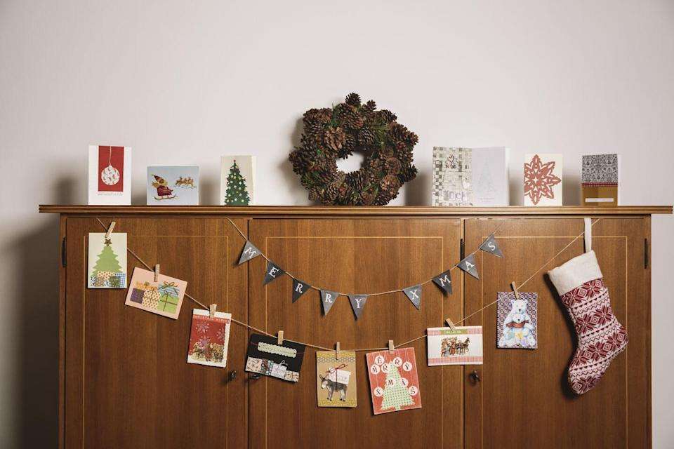 """<p>Don't just toss all of those adorable family Christmas cards into a basket somewhere—they deserve some daily attention. String some twine across a side table or along your stairway, then use clothespins to hang each special greeting. </p><p><a class=""""link rapid-noclick-resp"""" href=""""https://www.amazon.com/Boao-Christmas-Gloves-Snowflake-Clothespins/dp/B07V3KXD8Z/?tag=syn-yahoo-20&ascsubtag=%5Bartid%7C10072.g.34454588%5Bsrc%7Cyahoo-us"""" rel=""""nofollow noopener"""" target=""""_blank"""" data-ylk=""""slk:SHOP CHRISTMAS CLOTHESPINS"""">SHOP CHRISTMAS CLOTHESPINS</a></p>"""
