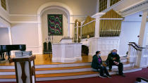 Maria Macario, left, talks with Rev. John Gibbons while seated on the steps to the altar at the First Parish church, Wednesday, Jan. 27, 2021, in Bedford, Mass. For three years, Macario has been too afraid to leave the confines of the church, which she moved in to avoid deportation, spending most of her time in a converted Sunday school classroom stocked with a hot plate, mini-fridge, TV and single bed. (AP Photo/Charles Krupa)