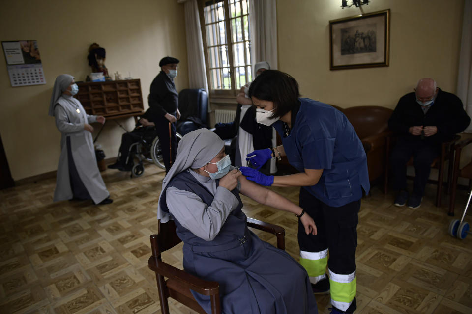 Nun Reyna Vasquez, worker at El Buen Pastor religious nursing home is vaccinated with Pfizer coronavirus vaccine, in Pamplona, northern Spain, Thursday Jan. 14. 2021. (AP Photo/Alvaro Barrientos)