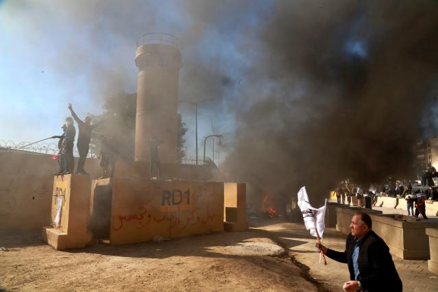 Protesters burn property in front of the U.S. Embassy compound in Baghdad on Dec. 31. (Photo: Khalid Mohammed/AP)