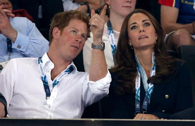 Kate Duchess of Cambridge talks to Prince Harry who points to a large video screen watch the early rounds of the men's and women's gymnastic competitions at the Commonwealth Games Glasgow 2014, in Glasgow, Scotland, Monday, July, 28, 2014. (AP Photo/Alastair Grant)