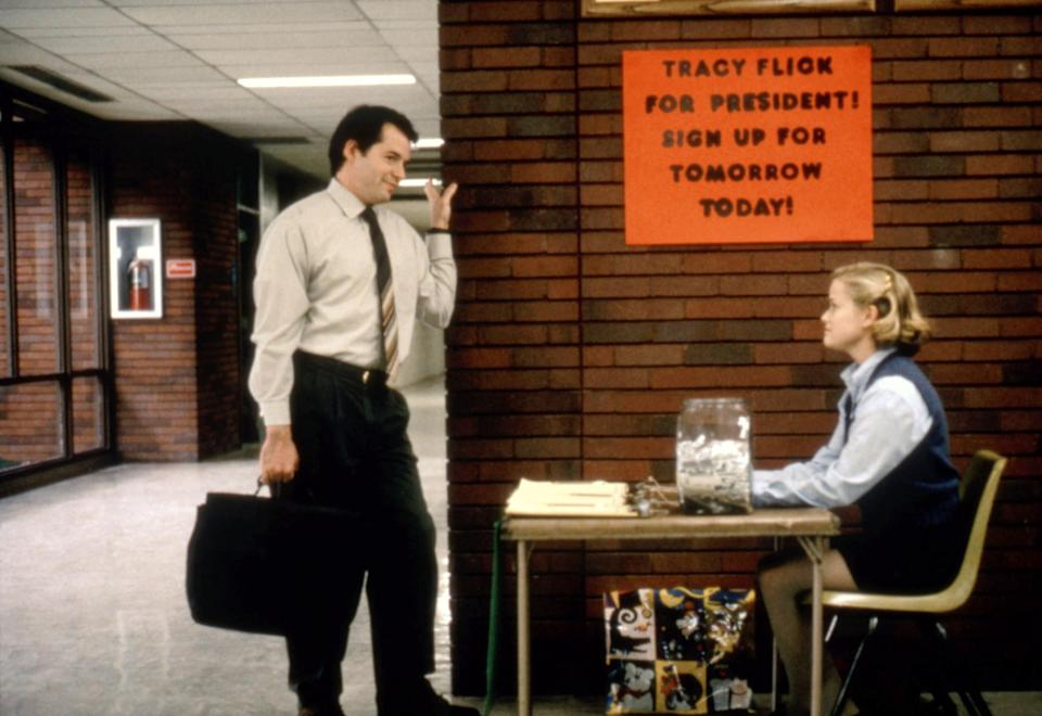 Matthew Broderick talks with Reese Witherspoon, who sits at a table in a school hallway