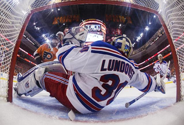 In this photo taken with a fisheye lens, New York Rangers goalie Henrik Lundqvist stops a shot against the Philadelphia Flyers in the second period in Game 3 of an NHL hockey first-round playoff series, Tuesday, April 22, 2014, in Philadelphia. (AP Photo/Chris Szagola)