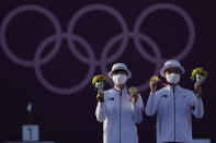 Gold medal winners South Korea's An San, left, and South Korea's Kim Je Deok celebrate on the podium of a mixed team competition at the 2020 Summer Olympics, Saturday, July 24, 2021, in Tokyo, Japan. (AP Photo/Alessandra Tarantino)