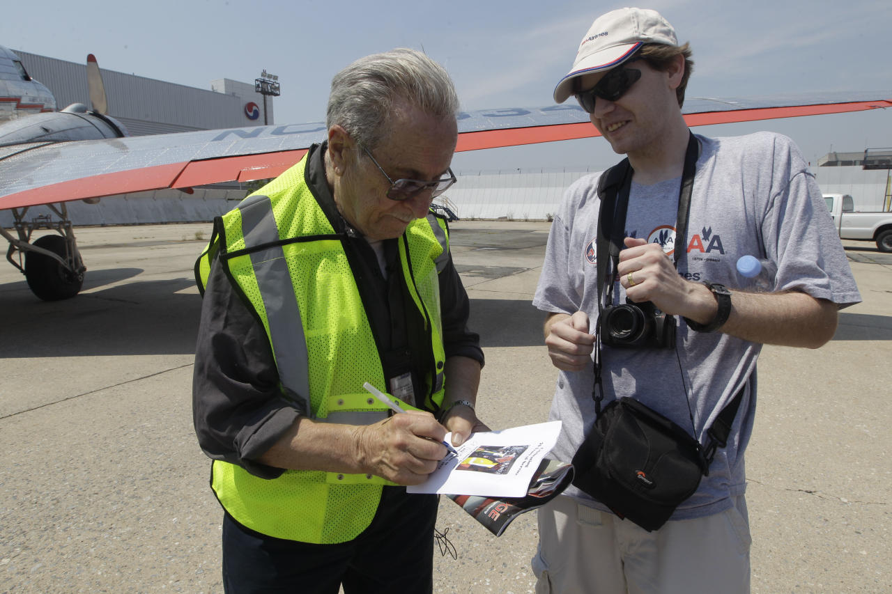 """Azriel """"Al"""" Blackman signs an autograph for an aviation enthusiast after flying in a DC-3, Wednesday, July 18, 2012 in New York. American Airlines is celebrating the 70-year service of a New York City mechanic who says he has no plans to retire. Azriel """"Al"""" Blackman was 16 years old when he started as an apprentice mechanic in July of 1942. (AP Photo/Mary Altaffer)"""