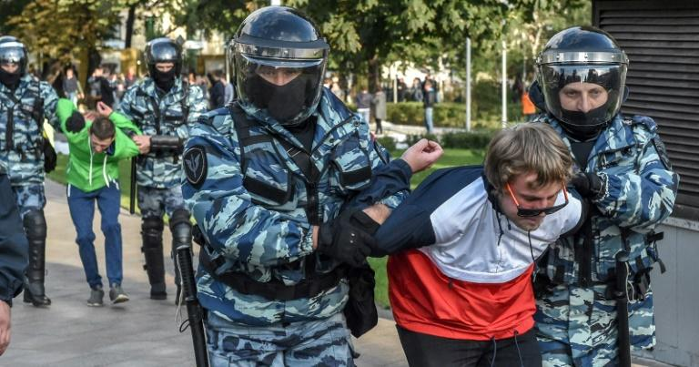 Russian National Guard officers detain protesters following a rally calling for fair elections in Moscow