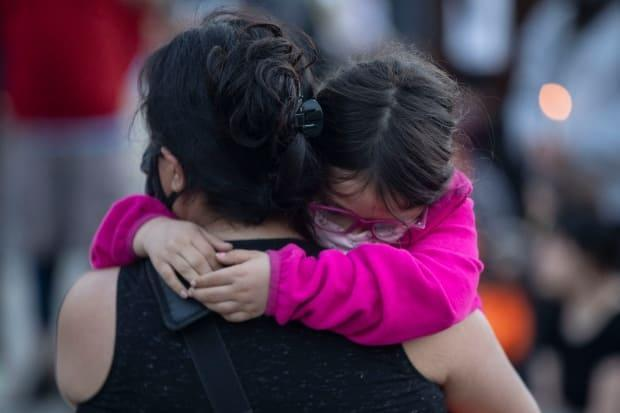 A mother hugs her daughter during a vigil in Toronto on May 30 after remains of children in unmarked burial sites were detected by the Tk'emlups te Secwépemc First Nation at the site of the former Kamloops Indian Residential School in B.C.'s southern Interior. The discovery is based on surveys using ground-penetrating radar and oral history of the school.  (The Canadian Press/Chris Young - image credit)