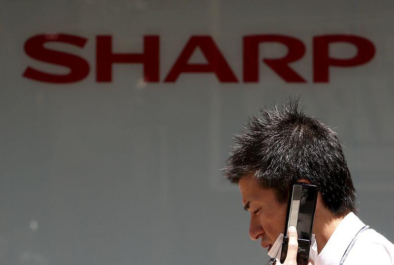 A man using his mobile phone walks under a logo of Sharp Corp outside an electronics shop in Tokyo