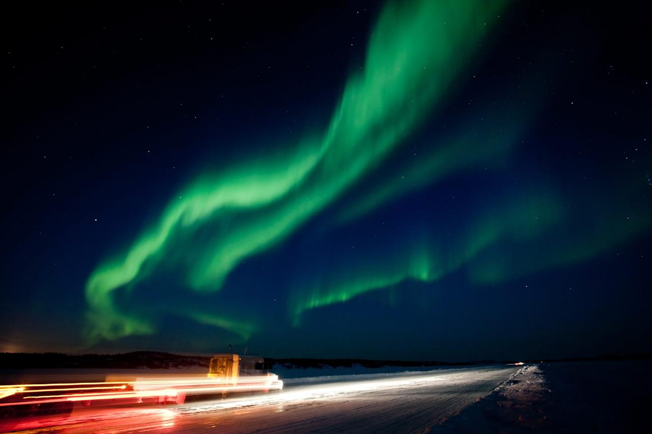 """The largest solar storm in five years sent a huge wave of radiation into earth's atmosphere creating a brilliant show of the aurora borealis near Yellowknife, North West Territories on Thursday March 8, 2012.  Yellowknife, which is situated directly under the auroral """"oval"""", has some of the best northern lights viewing in the world. Truckers returning from the diamond mines 330 kilometers northeast enjoy the nighttime spectacle as they cruised down the ice road on Prosperous Lake. (AP Photo/The Canadian Press, Bill Braden)"""