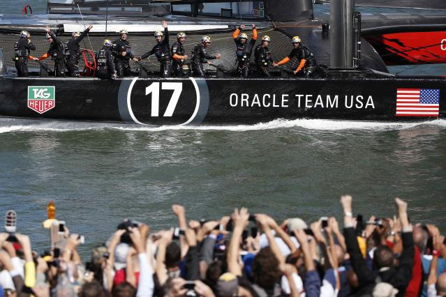 Members of Oracle Team USA wave to spectators after winning Race 18 of the 34th America's Cup yacht sailing race against Emirates Team New Zealand in San Francisco, California September 24, 2013. REUTERS/Stephen Lam (UNITED STATES - Tags: SPORT YACHTING)