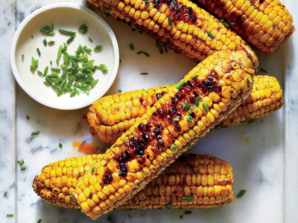 """<p>Seasoned with classic bold barbecue flavor, this <a href=""""https://www.myrecipes.com/summer-grilling/sides/cooking-corn-on-the-grill"""" rel=""""nofollow noopener"""" target=""""_blank"""" data-ylk=""""slk:grilled corn"""" class=""""link rapid-noclick-resp"""">grilled corn</a> will be a home run at your next backyard barbecue. Combined with the charred goodness from the grill, the trifecta of chili powder, cumin, and paprika create a spicy, smoky crust that makes this side irresistible. If <a href=""""https://www.myrecipes.com/summer-grilling/sides/cooking-corn-on-the-grill"""" rel=""""nofollow noopener"""" target=""""_blank"""" data-ylk=""""slk:you've never grilled corn before"""" class=""""link rapid-noclick-resp"""">you've never grilled corn before</a>, don't be alarmed by the pops. Just be sure to turn the ears occasionally to ensure nice, even cooking. Hit it with a squeeze of lime for extra flavor.</p>"""