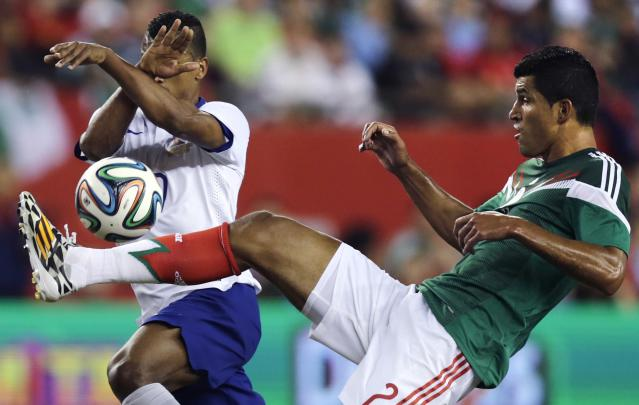 Portugal forward Nani, left, covers his face as Mexico defender Francisco Rodriguez kicks the ball during the first half of their friendly soccer match in Foxborough, Mass., Friday, June 6, 2014. (AP Photo/Charles Krupa)