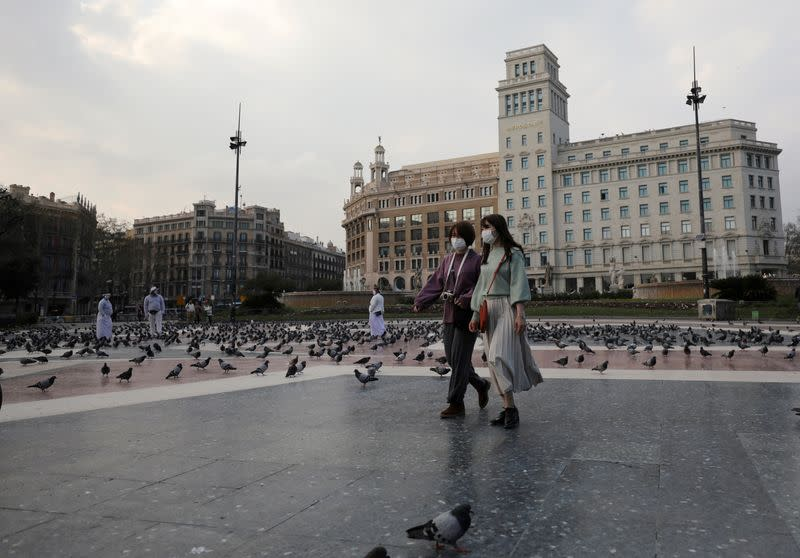 FILE PHOTO: Women wear protective face masks as they walk through an empty Plaza de Catalunya (Catalonia Square), amidst concerns over coronavirus outbreak, in Barcelona