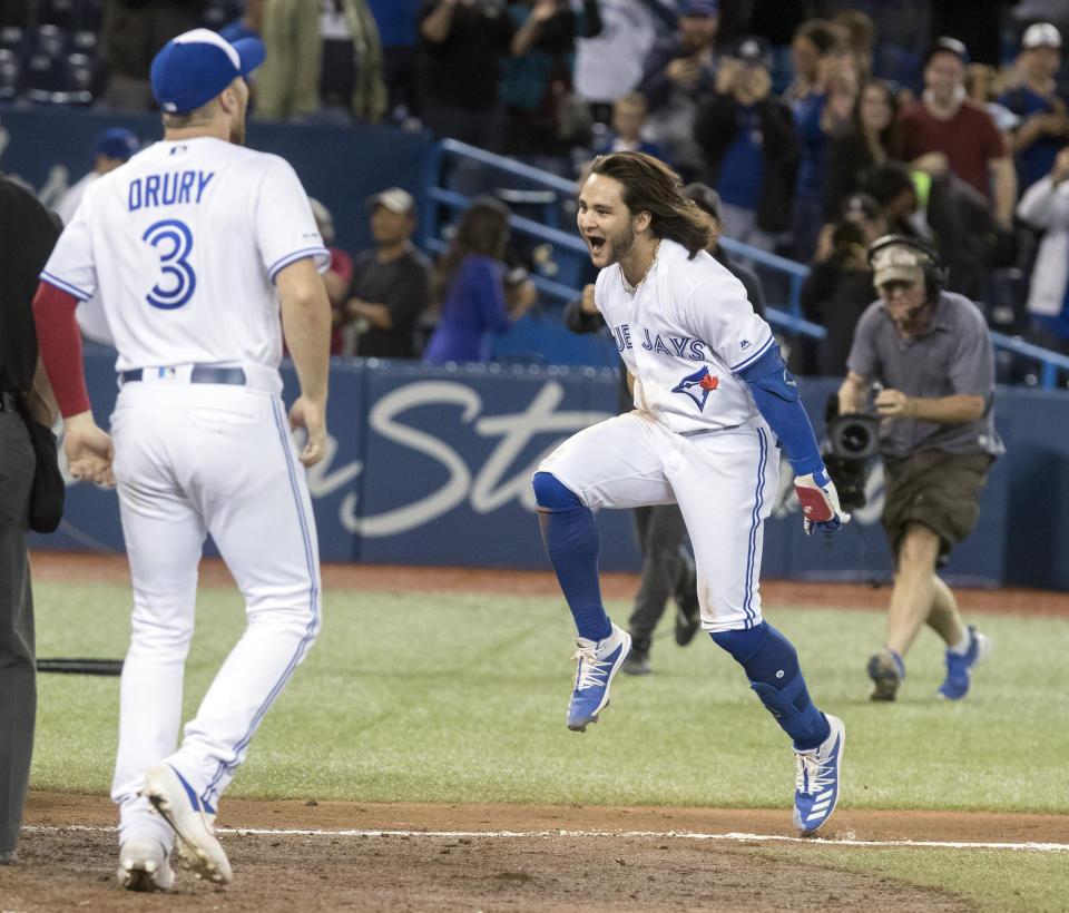 Toronto Blue Jays designated hitter Bo Bichette, front right, rounds the bases after hitting a walkoff home run to defeat the New York Yankees in the 12th inning of a baseball game in Toronto, Friday, Sept. 13, 2019. (Fred Thornhill/The Canadian Press via AP)