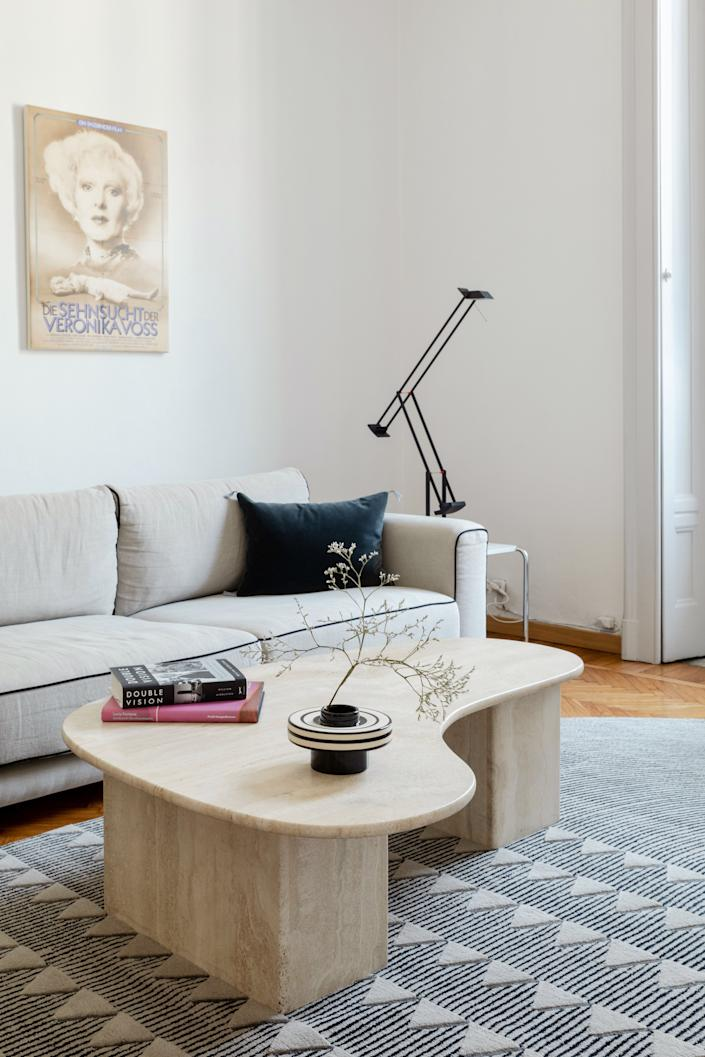 """<div class=""""caption""""> The living room is anchored by a <a href=""""https://www.cc-tapis.com/designer/david-nicolas/"""" rel=""""nofollow noopener"""" target=""""_blank"""" data-ylk=""""slk:David/Nicolas for CC-Tapis"""" class=""""link rapid-noclick-resp"""">David/Nicolas for CC-Tapis</a> rug and a 1970s Italian travertine coffee table. Alex found his sofa at <a href=""""https://www.caravane.co.uk/products/alto"""" rel=""""nofollow noopener"""" target=""""_blank"""" data-ylk=""""slk:Caravane"""" class=""""link rapid-noclick-resp"""">Caravane</a> and a <a href=""""https://www.dwr.com/lighting-desk-lamps/tizio-desk-lamp/2460.html?lang=en_US"""" rel=""""nofollow noopener"""" target=""""_blank"""" data-ylk=""""slk:Tizio desk lamp by Richard Sapper"""" class=""""link rapid-noclick-resp"""">Tizio desk lamp by Richard Sapper</a> sits atop <a href=""""https://www.knoll.com/product/laccio-side-table"""" rel=""""nofollow noopener"""" target=""""_blank"""" data-ylk=""""slk:Marcel Breuer's Laccio side table for Knoll"""" class=""""link rapid-noclick-resp"""">Marcel Breuer's Laccio side table for Knoll</a>. On display above the sofa are posters of films by <a href=""""https://filmartgallery.com/collections/fassbinder-rainer-werner"""" rel=""""nofollow noopener"""" target=""""_blank"""" data-ylk=""""slk:Rainer Werner Fassbinder from 1974 to 1982."""" class=""""link rapid-noclick-resp"""">Rainer Werner Fassbinder from 1974 to 1982.</a> </div>"""
