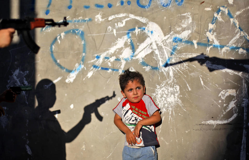 <p>A Palestinian boy reacts as youths frighten him by pointing their toy guns at him, in an alley in the West Bank refugee camp of Al-Amari in Ramallah, June. 16, 2009. (Photo: Muhammed Muheisen/AP) </p>