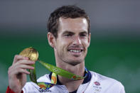 """FILE - Andy Murray, of England, smiles as he holds up his gold medal at the 2016 Summer Olympics in Rio de Janeiro, Brazil, in this Sunday, Aug. 14, 2016, file photo. Murray's been through two hip operations and assorted other injuries since he became the first tennis player with multiple Olympic singles golds by winning in 2012 and 2016. His ranking outside the Top 100, but past success — including three Grand Slam trophies — earned him a special spot in the Tokyo field for Britain. """"I just hope,"""" he said, """"the body holds up.""""(AP Photo/Charles Krupa, File)"""