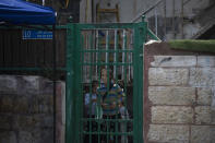 A child peers from the front gate of a Palestinian house occupied by Israeli settlers, days ahead of a court verdict that may forcibly evict Palestinian families from their homes in the Sheikh Jarrah neighborhood of Jerusalem, Friday, May 7, 2021. Dozens of Palestinian families in east Jerusalem are at risk of losing their homes to Jewish settler groups following a decades-long legal battle. The threatened evictions have sparked weeks of protests and clashes in recent days, adding to the tensions in Jerusalem. (AP Photo/Maya Alleruzzo)