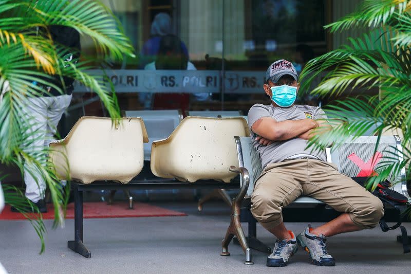 A man wearing a protective face mask sits on a chair while maintaining social distance amid the coronavirus disease (COVID-19) pandemic in Jakarta