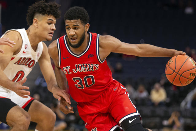FILE - In this Dec. 21, 2019, file photo, St. John's guard LJ Figueroa (30) tries to drive past Arizona guard Josh Green (0) during the first half of an NCAA college basketball game in San Francisco. Figueroa has declared for the NBA draft. School officials announced Figueroa's decision Saturday, March 28, 2020, saying that he hasn't hired an agent and still has the option to return to school. (AP Photo/D. Ross Cameron, File)