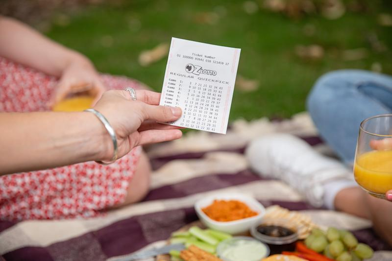 Pictured is a woman holding an Oz Lotto ticket at a picnic. Source: The Lott/file picture