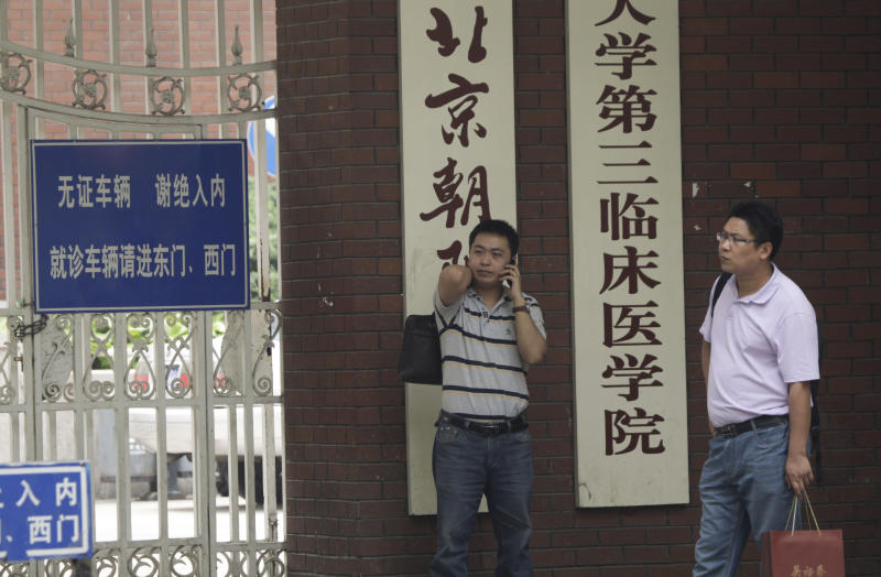 Chinese talks on a mobile phone outside a hospital where Chinese legal activist Chen Guangcheng is receiving medical treatment in Beijing, Wednesday, May 9, 2012. Chen who triggered a diplomatic dispute between China and the United States said Monday he is confident that Beijing will hold up its end of a tentative deal to let him study overseas. (AP Photo/Vincent Thian)
