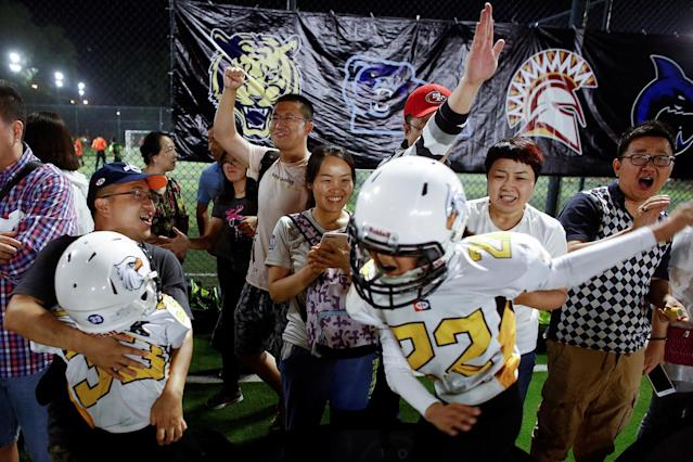 <p>Eagles players celebrate their win over the Sharklets in their Future League American football youth league match in Beijing, May 26, 2017. (Photo: Thomas Peter/Reuters) </p>