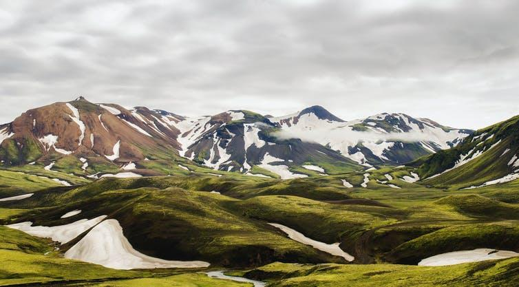 Large mountains with glaciers, grassy hills in foreground.