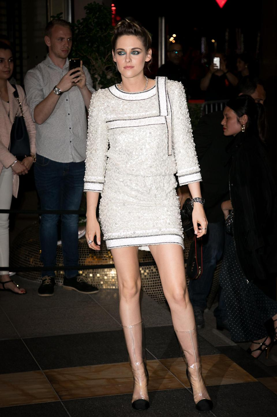 <p>Arrivin at the Chanel And The Vanity Fair France Party, Kristen Stewart took her hemline shorter wearing a sequinned mini dress by Chanel which she wore with the brand's iconic plastic boots. <br><em>[Photo: Getty]</em> </p>