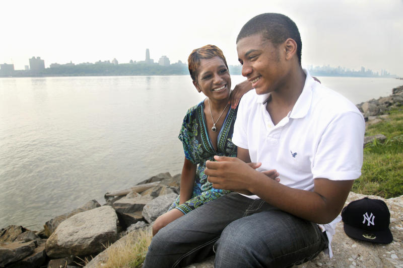 Rachel Noerdlinger and her son Khari, 14, share a moment at the edge of the Hudson River near their home in Edgewater, N.J., across from Harlem, N.Y., on Tuesday, June 28, 2011. Noerdlinger previously lived in Harlem for 16 years before moving to Edgewater with her son.  (AP Photo/Bebeto Matthews)