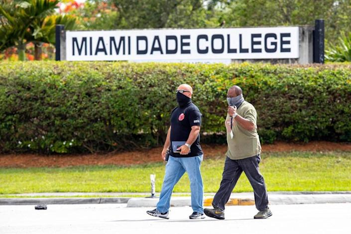 Detectives cross the street where squad cars and other official vehicles block traffic on 104th street outside the Shell gas station and across the street from Miami-Dade Kendall Campus near the crime-scene after another Miami-Dade mass shooting and a possibly connected car crash killed three people and sent five or six others to the hospital with gunshot wounds, around Grand Salon Reception Hall at Southwest 104th Street and 109th Court in the Kendall neighborhood of Miami, Florida, on Sunday, June 6, 2021.