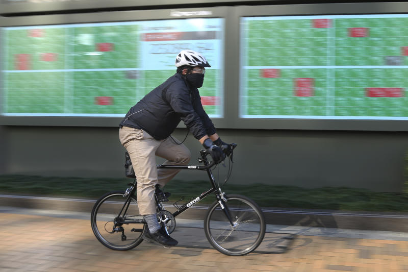 A man cycle pasts by an electronic stock board of a securities firm in Tokyo, Tuesday, Dec. 3, 2019. Asian shares slipped Tuesday, following a drop on Wall Street amid pessimism over U.S.-China trade tensions. (AP Photo/Koji Sasahara)