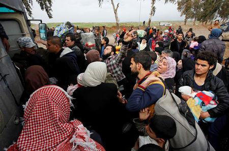 Displaced Iraqi people from different areas in Mosul wait to be transferred to a safe area during a battle between Iraqi forces and Islamic State militants, in the city of Mosul