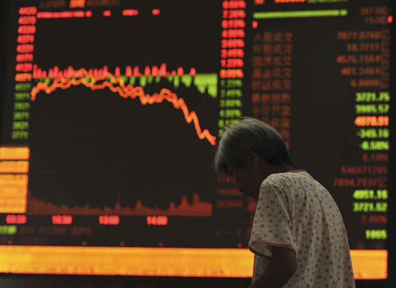 An investor stands in front of an electronic board showing stock information at a brokerage house in Qingdao