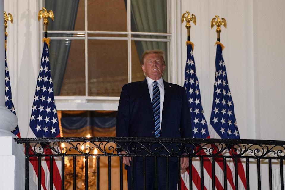 US President Donald Trump looks out from the Truman Balcony as he arrives at the White House upon his return from Walter Reed Medical Center, where he underwent treatment for Covid-19, in Washington, DC, on October 5, 2020. (Photo by NICHOLAS KAMM / AFP) (Photo by NICHOLAS KAMM/AFP via Getty Images)