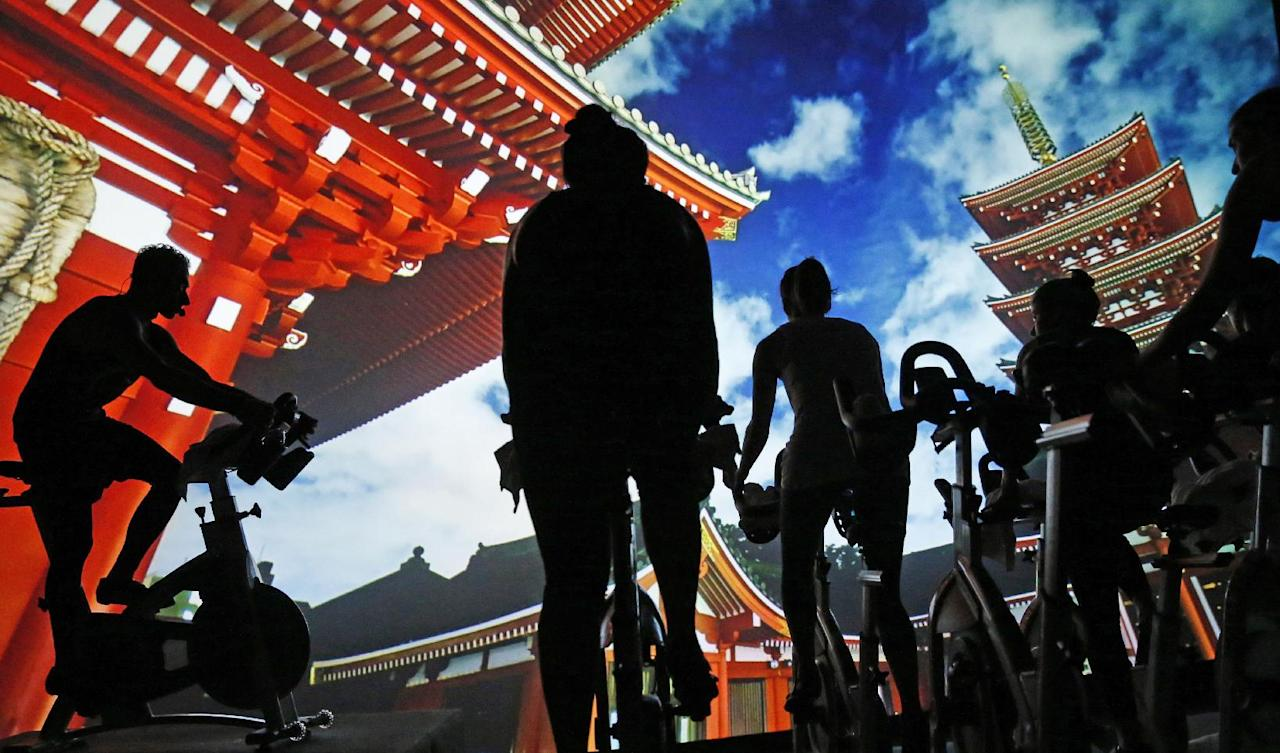 In this Jan. 3, 2017 photo, creative director and master instructor Jesse Alexander, far left, leads a spinning class at Brooklyn's IMAXShift in New York, as an image from Asia is projected on the screen. Participants cycle on stationery bicycles to booming music while images flash by on an IMAX screen in a tiered, theatre-like setting. Stunning visuals of the solar system, soaring shots of the the word's major cities, shots of the Hawaiian coastline and other pastoral scenes alternate with with music-reactive visuals timed to the instructor's choreography for a sensory overloading experience. (AP Photo/Kathy Willens)