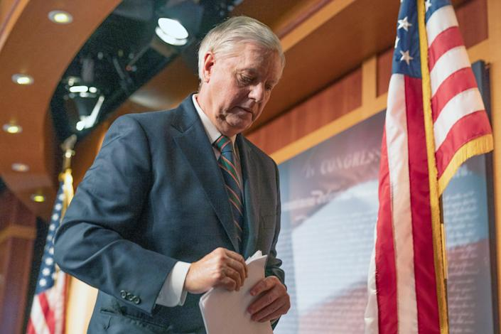 Lindsey Graham walks away after speaking to reporter on 7 January about Capitol violence. (AP)