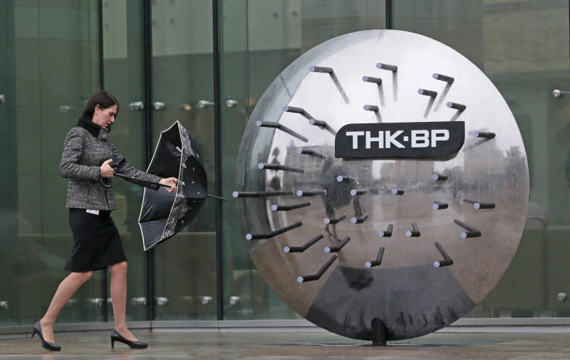 FILE - In this Oct. 18, 2012 file photo, a woman walks outside the TNK-BP headquarters in Moscow, Russia. British oil company BP says it has agreed to sell its stake in its TNK-BP joint venture to Russian oil company Rosneft for US$17.1 billion in cash and a 12.84 percent stake in Rosneft. BP announced Monday, Oct. 22, 2012, that it would use some of the money to buy more shares in Rosneft to raise its stake to 19.75 percent. (AP Photo/Mikhail Metzel, File)