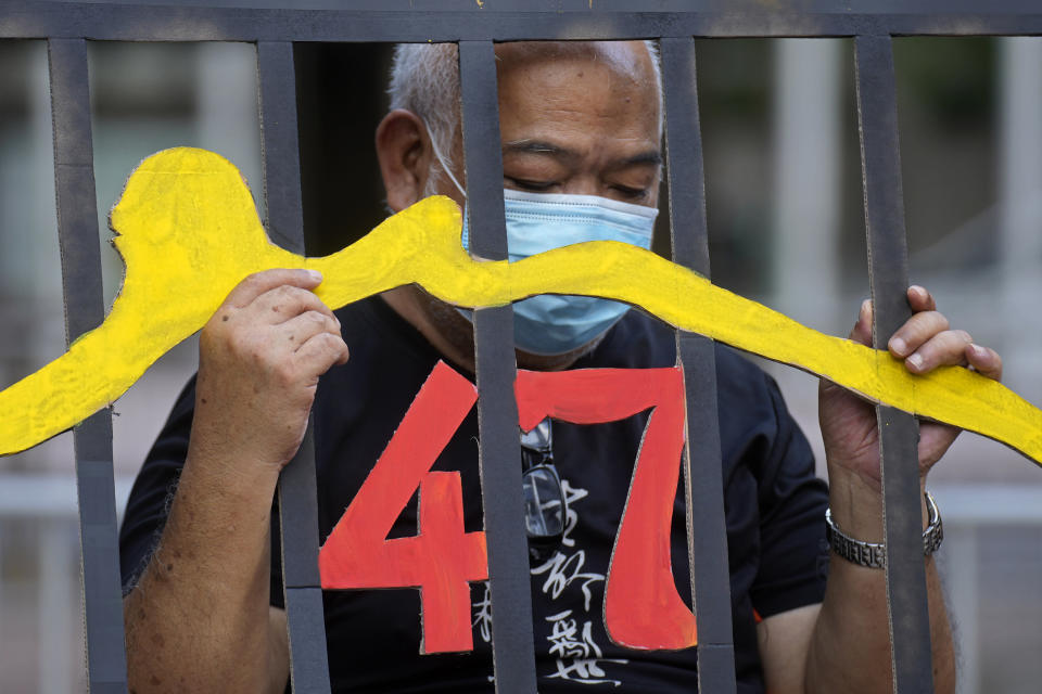 """A protester stands behind a mock prison during a protest against an election committee that will vote for the city's leader in Hong Kong Sunday, Sept.19, 2021. Hong Kong's polls for an election committee that will vote for the city's leader kicked off Sunday amid heavy police presence, with chief executive Carrie Lam saying that it is """"very meaningful"""" as it is the first election to take place following electoral reforms. (AP Photo/Vincent Yu)"""