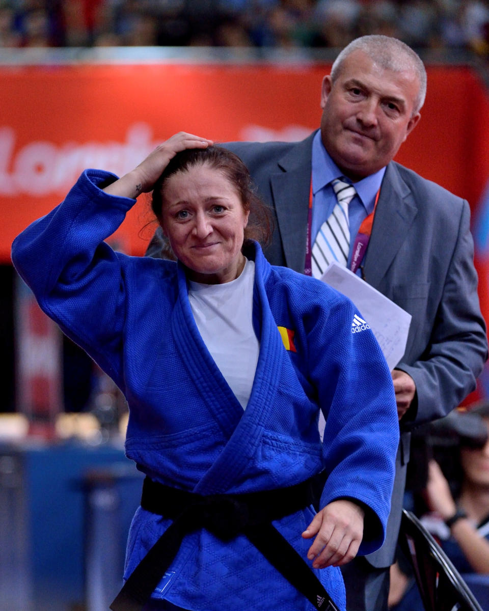 LONDON, ENGLAND - JULY 30: Silver medalist Corina Caprioriu of Roumania leaves the mat after her semi-final victory in the Women's -57kg Judo followed by her coach on Day 3 of the London 2012 Olympic Games at ExCeL on July 30, 2012 in London, England. (Photo by David Finch/Getty Images)