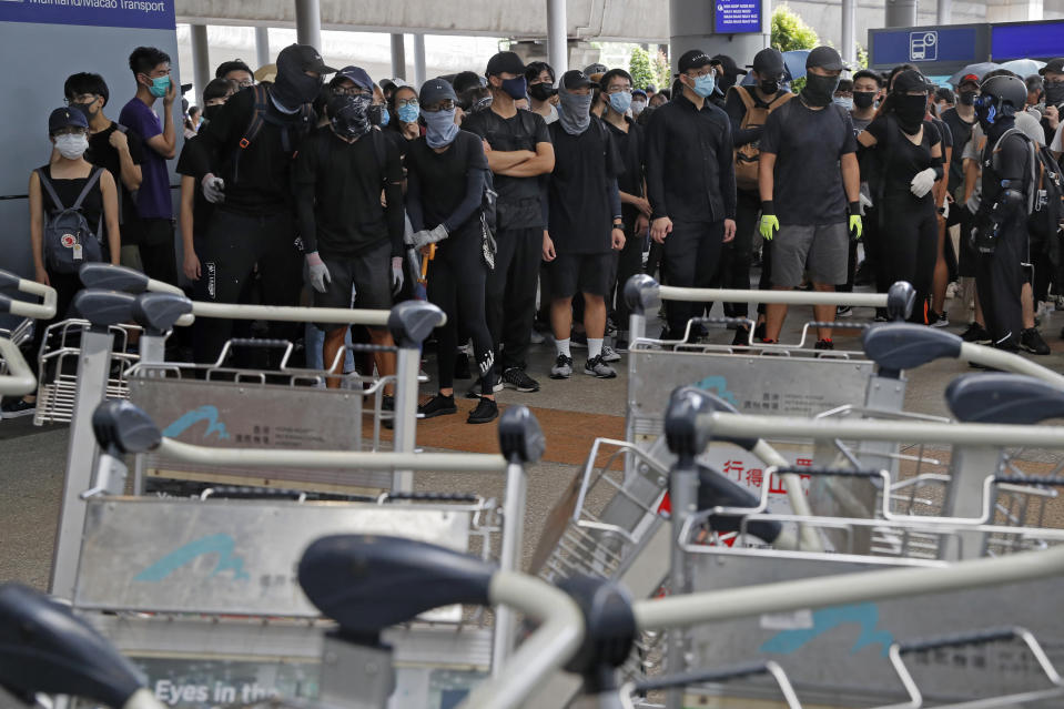 Pro-democracy protestors block a road outside the airport in Hong Kong, Sunday, Sept. 1, 2019. Train service to Hong Kong's airport was suspended Sunday as pro-democracy demonstrators gathered there, while protesters outside the British Consulate called on London to grant citizenship to people born in the former colony before its return to China. (AP Photo/Kin Cheung)