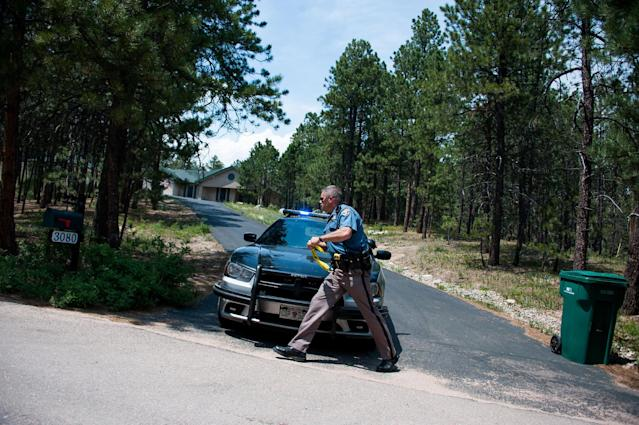 A Colorado State Patrol officer races to leave a mark on a mailbox to note that the residents of the house have been notified of the mandatory evacuation because of the Black Forest fire and have left the area, Thursday, June 13, 2013, north of Colorado Springs, Colo. A voracious wildfire driven in all directions by shifting winds destroyed at least 360 homes — a number that was likely to climb as the most destructive blaze in Colorado history burned out of control for a third day through miles of tinder-dry woods. (AP Photo/The Colorado Springs Gazette, Michael Ciaglo) MAGS OUT