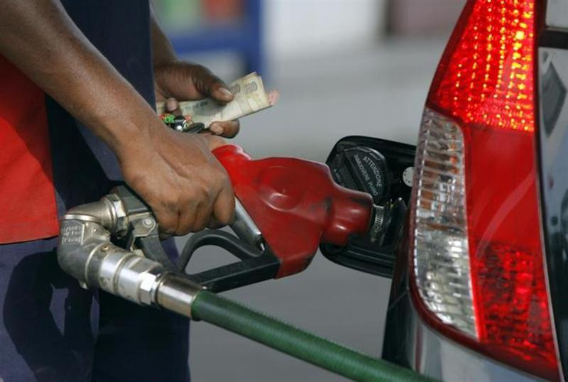 An employee fills a vehicle with fuel at a station in New Delhi June 25, 2010. REUTERS/Mukesh Gupta/Files