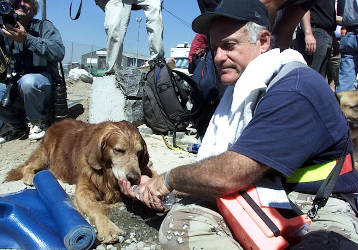 """Scott Shields, right, gives his rescue dog """"Bear"""" water from a bottle after coming out the World Trade Center disaster site in this Sept. 13, 2001 file photo. The North Shore Animal League America has offered to pay medical bills and provide lifetime care for Bear, the famous search dog that suffers from ailments his owner says were incurred during recovery work at the World Trade Center site. (AP Photo/Beth A. Keiser, FILE )"""