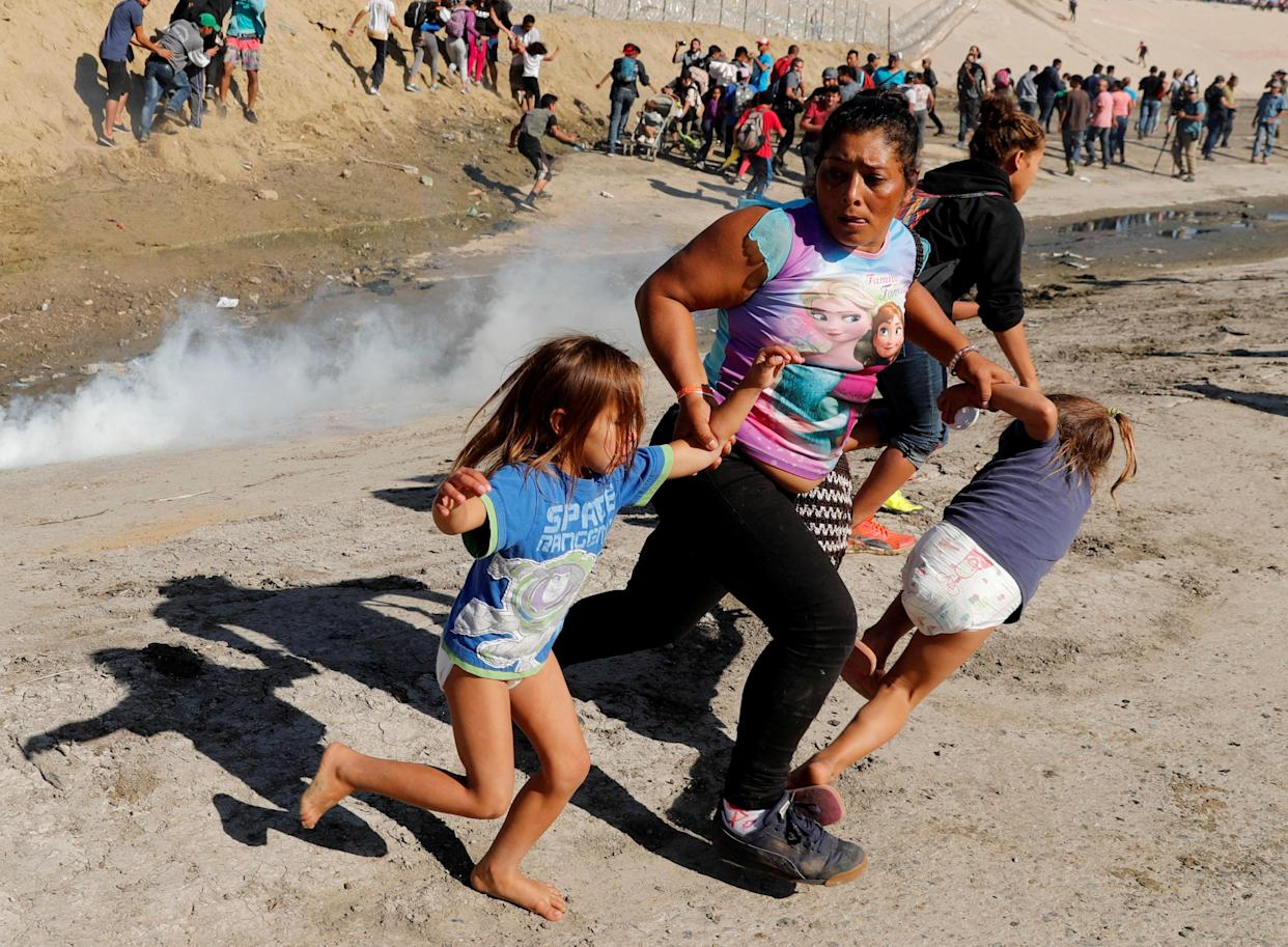 A migrant family from Honduras, part of a caravan of thousands traveling from Central America en route to the U.S., runs from tear gas released by U.S. border patrol agents near the fence between Mexico and the U.S. in Tijuana, Mexico, on Sunday. (Photo: Kim Kyung-Hoon/Reuters)