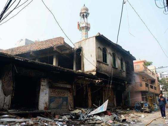 Flags can be seen on the burnt-out mosque's minaret in the Ashok Nagar neighbourhood (AFP/Getty)