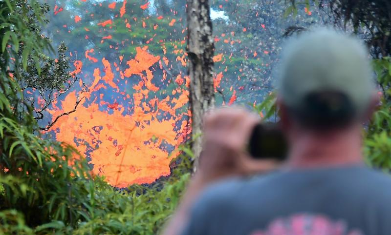 A man watches as lava spews from a fissure in the Leilani Estates area (AFP Photo/Frederic J. BROWN)